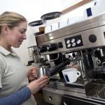 Mede-eigenaresse Tiffany Aerts bereidt een melkkoffie bij haar koffiemachine. Het gaat hier om een verhaal over de melk. Oppassen dat je niet alleen haar rug ziet, ik wil ook een deel van haar gezicht zien. De foto is actief.